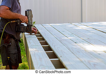 Building a backyard deck with worker putting with nail gun patio construction terrace