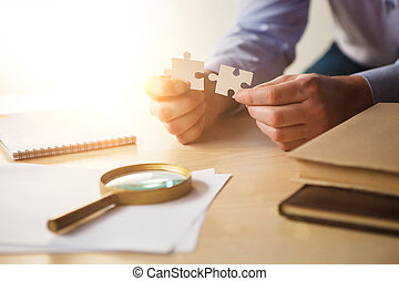 Building a business success. The hands with puzzles -...