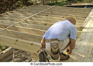 Building a Deck - A man bent over working on a half finished...