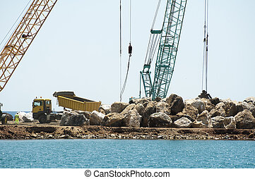 Building a dike. Cranes and excavator put stones in the sea....