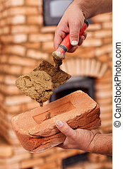 Building a masonry heater - closeup on worker hands holding...