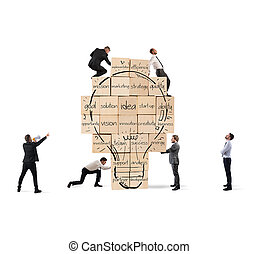 Building a new creative idea. Business person built together a big brick wall with drawn lightbulb