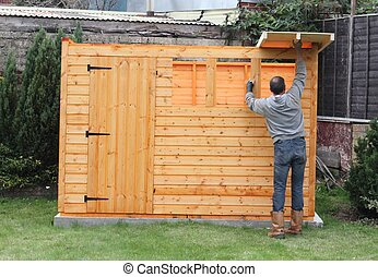 Building a wooden shed and putting on the roof