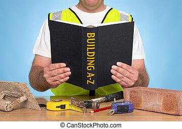 A builder sat at a desk reading a BUILDING A-Z book
