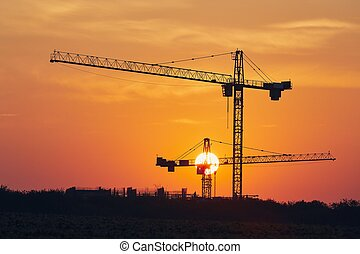 Building activity on contruction site. Silhouettes of cranes against sun.