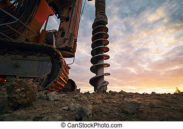 Building activity on contruction site. Close-up view of drilling machine.