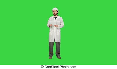 Building Architect Master Engineer Looking Paper Plan Under Development Area on a Green Screen, Chroma Key.