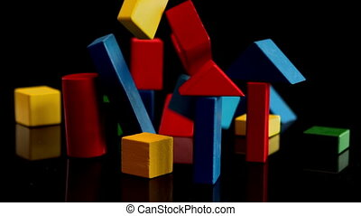 Building blocks falling and bouncing on black background in...