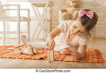 Building collapse games - Little girl playing with wooden...