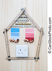 Building Components Arranged In Shape Of House On Wooden Background