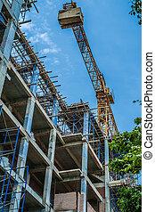 Building construction site and crane against blue sky