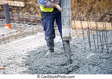 building construction worker pouring cement or concrete with...