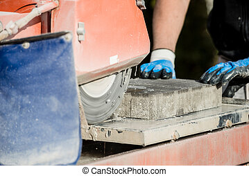 Building contractor using an angle grinder to cut a paving stone