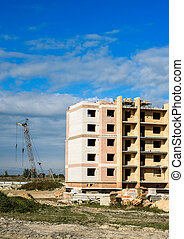 Building crane and apartment house under construction against sky