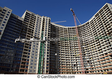 Building crane at the background of building under construction