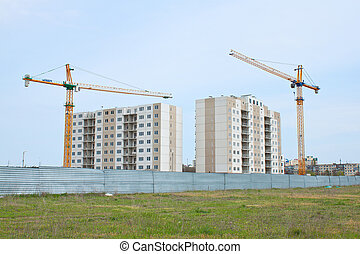 Building cranes above the unfinished apartment house. -...