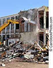 An excavator demolishing a two story concrete building