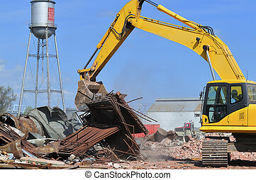 Building demolition site - An excavator sorting waste at a...