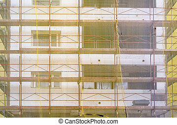 Building facade renovation, old house reconstruction, repair. Scaffold in front of building facade covered with yellow transparent fabric