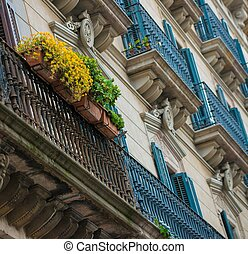 Building facade with beautiful balcony full of flowers