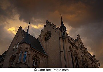 Building Gothic style with dark clouds hanging.
