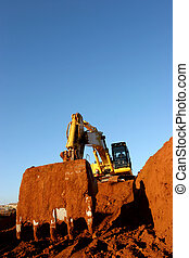 Building Ground - Heavy construction equipment digging into...