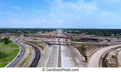 Drone aerial view of building highway, motorway or expressway in summer.