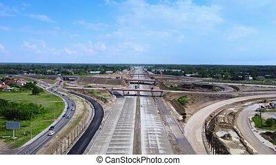 Building highway, motorway or expressway in summer. Drone aerial view.