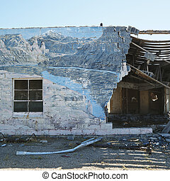Falling down building with winter scene mural painted on side.