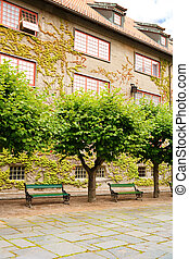 Building in Norsk Folkenmuseum - Building, benches and trees...