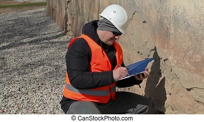 Building inspector check old building's wall