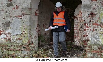 Building inspector checking documentation at old ruins