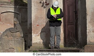 Building inspector checking documentation near building door