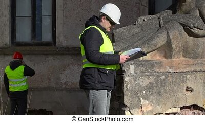 Building inspector checking old monument near building
