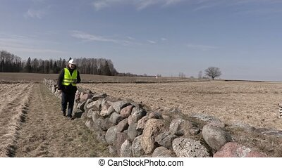 Building inspector checking stone wall