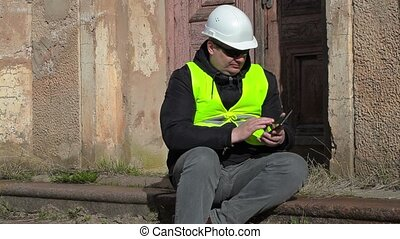 Building inspector sitting and take picture on smart phone
