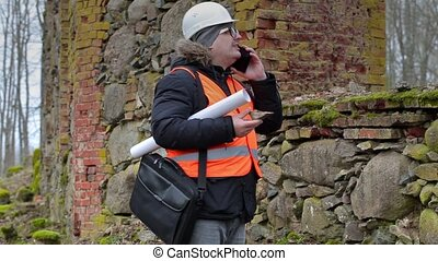 Building inspector talking on smart phone near old ruins