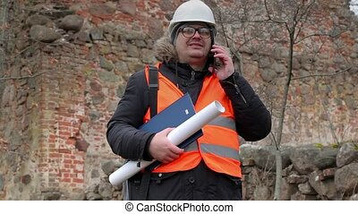 Building inspector using smart phone at old ruins