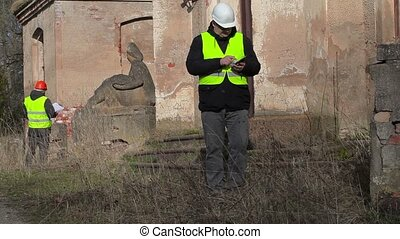 Building inspector using tablet PC at the old manor