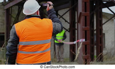 Building inspector with camcorder and with worker in...