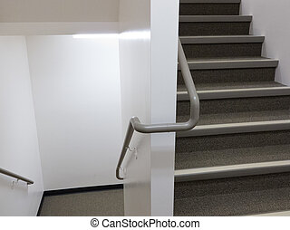 Flight of stairs in well lit building with safety banister handrails on both sides