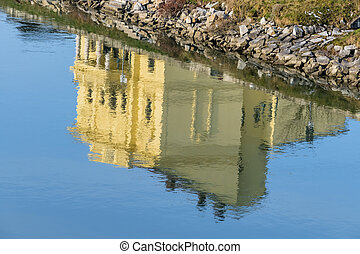 building is reflected in the water