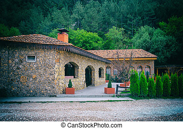 Building made of stone on a background of green forest. Resting-place.