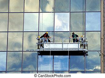 Building Maintenance - Two men raise the scaffolding that...