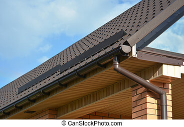 Building Modern House Construction with metal roof corner, rain gutter system and roof protection from snow board, snow bar (Snow guard). Roof Snow Guards: Building Materials & Supplies
