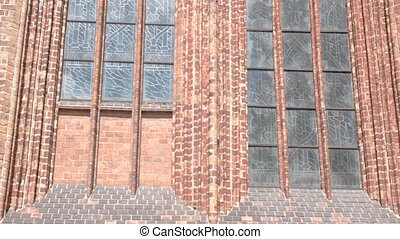 Building of red brick. Pattern on tall windows. Example of...
