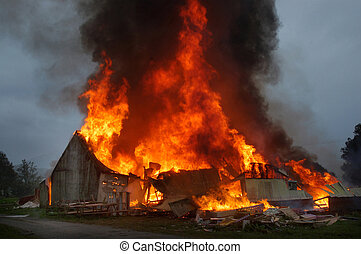 building on fire - flames and smoke rise from burning farm...