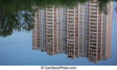 Building reflected in the water, rock dropped in the water