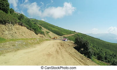 Building roads in mountains - Descent of mountain road under...