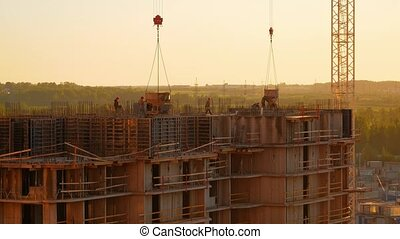 Building site at sunset. A brigade of workers is pouring...
